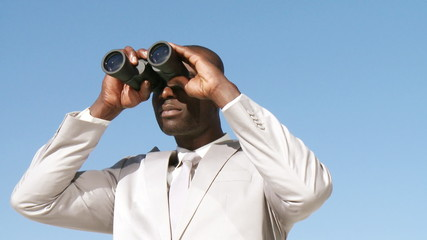 african businessman looking through spyglasses