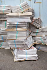 Bundles of newspapers stacked in an urban setting