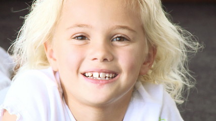 cute blond little girl smiling at the camera