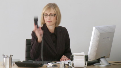 woman sitting in her office answering to the phone