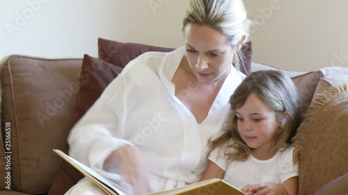 mother and daughter reading together sitting in the sofa