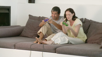 energetic couple playing video games sitting in sofa