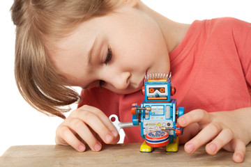 little girl in red T-shirt plays with clockwork robot isolated