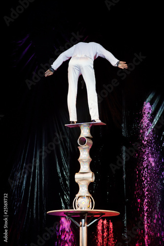 equilibrist skillfully balances in circus - 25169732