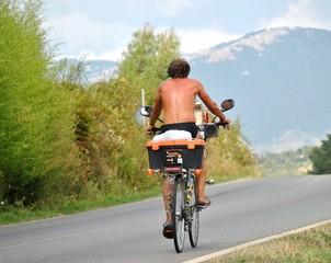 Ciclista in costume su strana bicicletta
