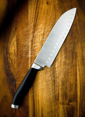 Large stainless steel santoku knife on wooden chopping board