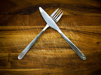 Stainless steel cutlery on a wooden chopping board