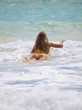 blond girl in bikini paddles her surf board towards the waves