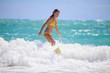 teenage girl in a yellow bikini surfing in Hawaii