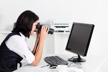 businesswoman looking at computer through binoculars