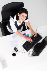 overhead of businesswoman working at desk