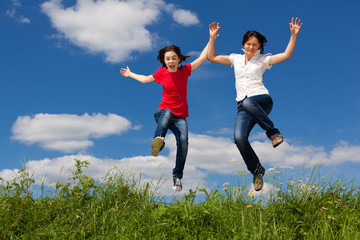 Girls jumping, running against blue sky