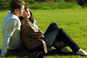 young couple sitting on the green grass