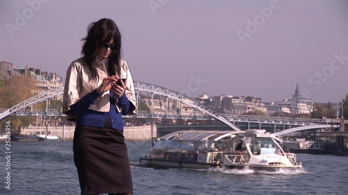 Businesswoman making a cellphone call along the Seine river