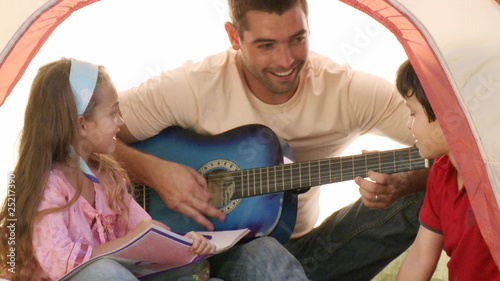 Two happy kids with their dad playing the guitare