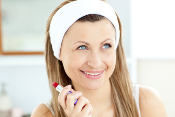 Bright young woman using a red lipstick in the bathroom