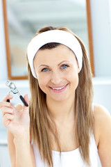Smiling woman holding an eyelash curler looking at the camera in