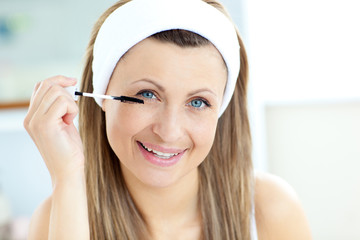 Happy young woman using mascara in the bathroom
