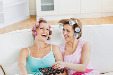 Laughing female friends with hair rollers eating chocolate at ho