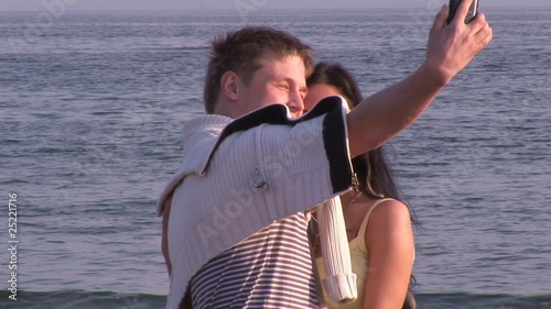 attractive young couple taking picture on the beach