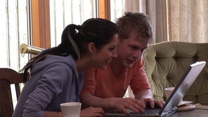 couple at home working on laptop sitting in the dining room