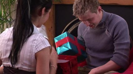 young couple exchanging presents during christmas