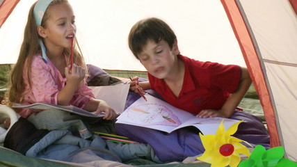 adorable sibling playing in a tent in their garden