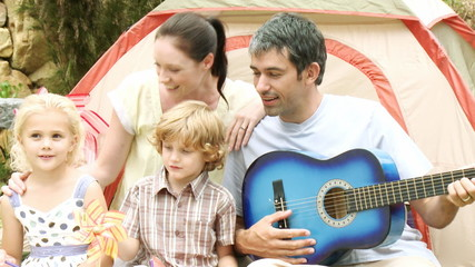 family singing with guitar during camping