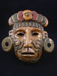 Clay mask of a Maya warrior with tattoos and ear spools.
