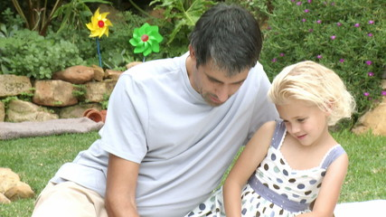father and daughter drawing in the garden