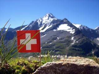 Schweizer Flagge vor Alpenkulisse