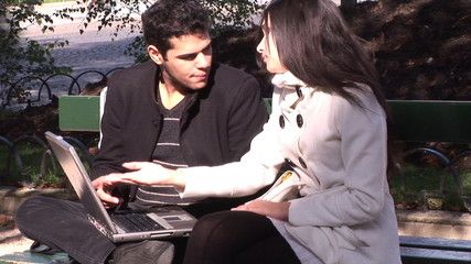 two hispanic students using laptop sitting in a park in France