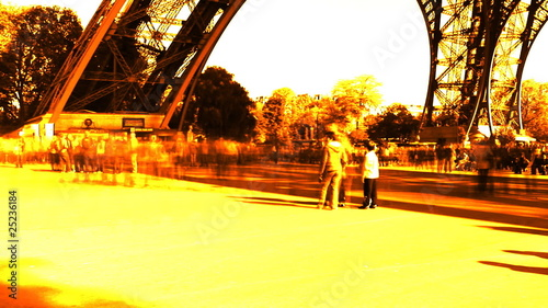 An orange fast moving Crowd Underneath the Eiffel Tower