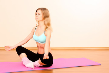 Young blond woman in lotus pose
