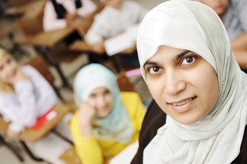Muslim female teacher in classroom with children pupils