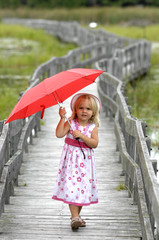 Little blond girl with red umbrella