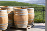 wooden wine barrels with view of winery in background