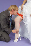 Amusing groom removes a garter from leg of bride