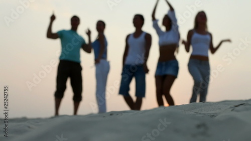 A group of young people dancing on the beach at sunset