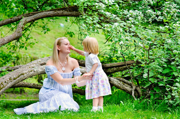Mother and daughter sit on grass in a beautiful blooming garden