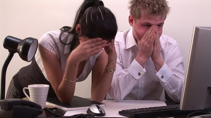 two stressed businesspeople in front of computer