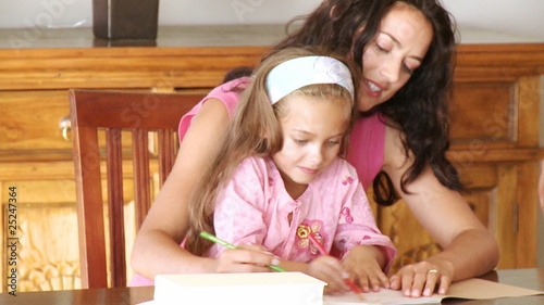mother writing with her daughter on her knees