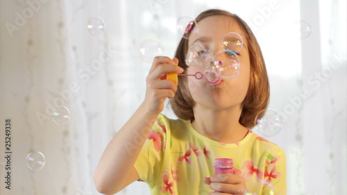 Little girl blows soap bubble