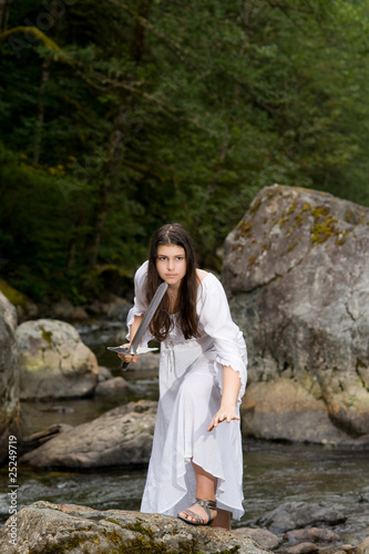 Young girl in white dress with two handed sword