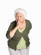 Senior woman making gesture for quiet isolated against white