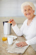 Happy elderly woman having her breakfast at home