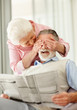 A mature woman covering a senior man's eyes to surprise him
