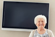 Happy senior woman against huge plasma TV screen - copyspace