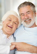 Smiling senior female sitting with a loving mature man at home