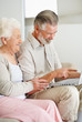 Relaxed mature woman with a happy senior man working on laptop